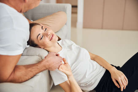 Blissful young woman with her eyes closed resting on the edge of sofa with her caring boyfriend