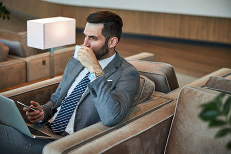 Fashionable businessman in a grey suit and tie making a sip of tasty coffee while working with his gadgets