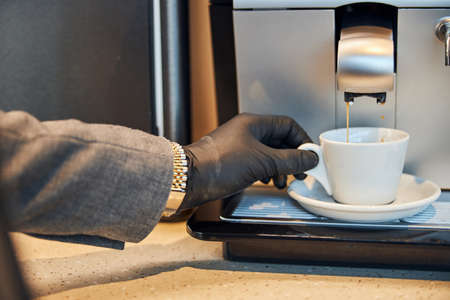 Hand in a black leather glove seizing a cup with coffee flowing into it Archivio Fotografico