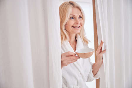 Waist-up portrait of a merry lady in a terry bathrobe standing in a beauty salon Standard-Bild
