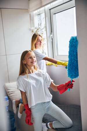 Joyous pretty girl with a microfiber duster and her female parent with a cloth dusting the kitchen