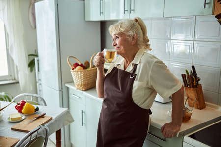 Joyful elderly lady in apron enjoying morning hot drink and smiling while spending time at home