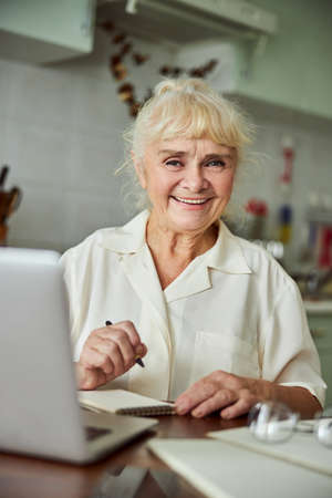 Joyful elderly lady holding pen and smiling while sitting at the table with modern laptop Banque d'images