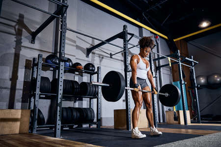 Concentrated African American female weightlifter holding the loaded barbell with both hands at the gym