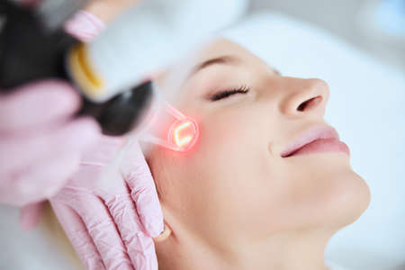Close up portrait of a young woman patient receiving a laser treatment in a spa salon