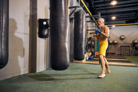 Full-sized portrait of a focused barefoot kickboxer standing before the punching bags in an upright stance