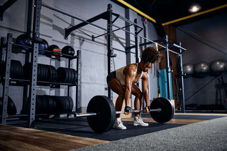 Serious muscular African American lady lifting the loaded barbell off the ground with both hands