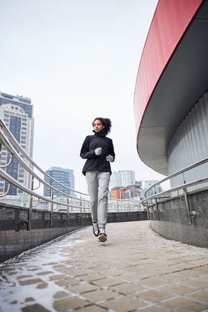 Athletic female energetically moving through the sloping concrete walkway next to a building Stock Photo