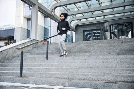 Sportsperson moving from the stairs with a handrail, leading to a glass revolving door