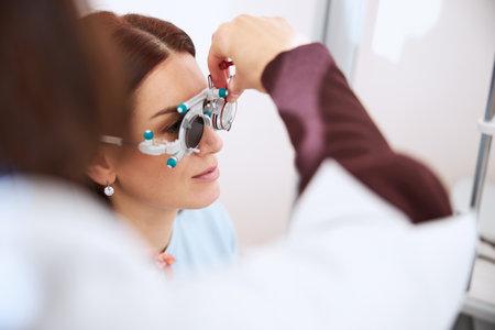 Eye doctor inserting the trial lens in a left eye socket of glasses for testing eyesight