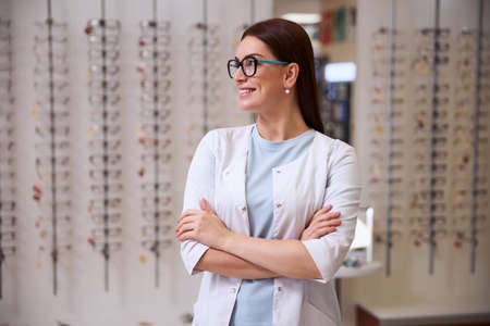 Eye doctor wearing glasses while staring sideways and holding her hands on a chest level