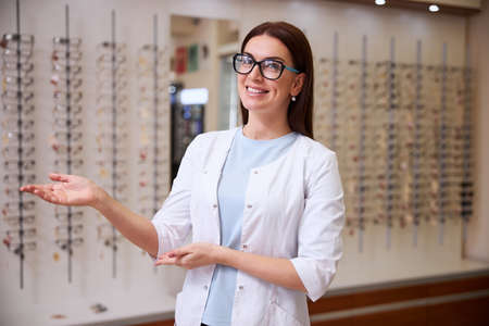 Female ophthalmologist showing around her store and asking to look at many glasses on the rack Zdjęcie Seryjne