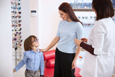 Parent placing her hand on boy shoulder while approving his new look in glasses with a label