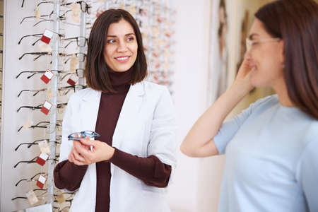 Woman wearing a model of glasses while an optician getting ready a new pair