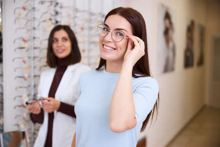 Energetic adult bringing up her hand and touching the side of glasses with an oculist staying behind