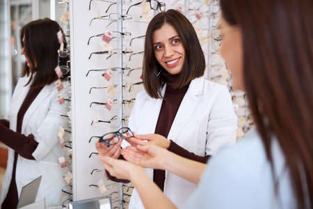 Helpful eye care professional taking the eyeglasses pair from a visitor with a smile on her face Zdjęcie Seryjne