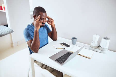 Male putting his fingers to the sides of a head and concentrating on his work ahead Stock Photo