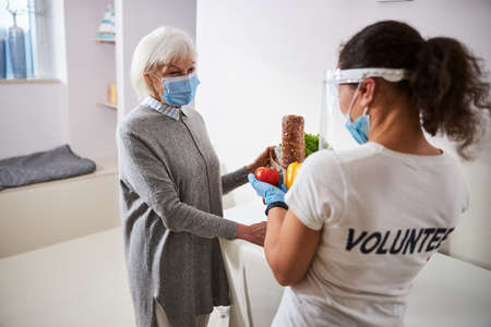 Woman in a disposable medical mask gazing at a young caregiver with groceries in her hands