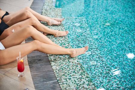 Cropped photo of women legs splashing in blue pool water at a nice resort