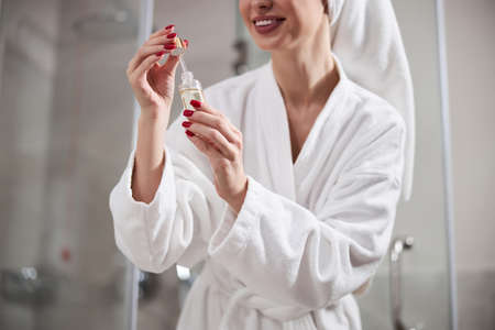 Cropped photo of young woman in comfortable white bathrobe standin in bathroom and looking at cosmetic product