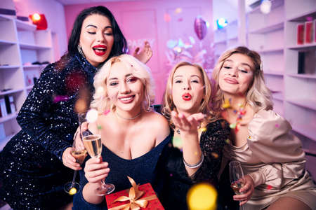Front view of a smiling woman enjoying her birthday party with her pleased female friends Imagens