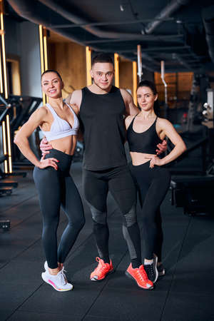 Full length portrait of happy athletic two women and man working as fitness instructors in sport studio