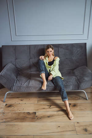Female having a seat with one leg on a sofa and another on a floor while watching straight