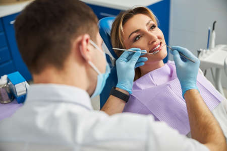 Man in medical clothes putting a sickle probe and dental mirror inside a mouth of a satisfied woman