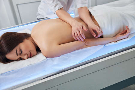 Masseur bending over client and putting arms on a lower part of back for deep tissue massage