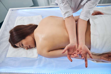 Masseuse keeping patient back under pressure by putting two forearms on it and leaning weight of her body on them Zdjęcie Seryjne