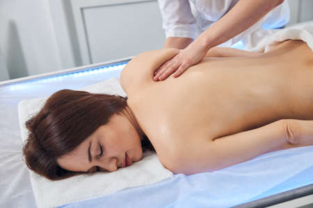 Hand of massagist gathering skin tissue of shoulder blade between the fingers during a classic massage