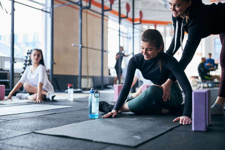 Friendly female coach helping women out while assisting them at the gym