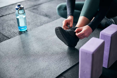 Croppe photo of a lady tying her shoelaces on a black sneaker whie sitting on sports mat Archivio Fotografico