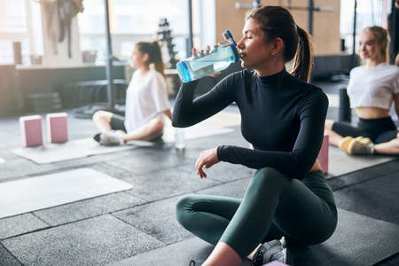 Mindful young lady sipping water from her bottle while taking a break from working out Archivio Fotografico