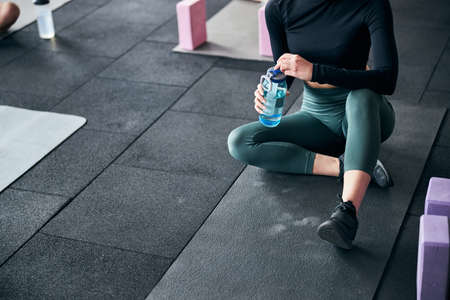 Cropped photo of a slim young lady in sporty outfit sitting on mat and holding water bottle