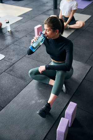 Young brunette lady in athletic wear sipping water from her water bottle while sitting on fitness mat Archivio Fotografico