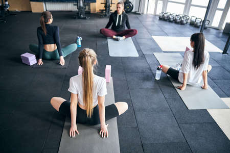 Rear-view photo of slim young ladies practising stretching for a lotus pose in yoga class