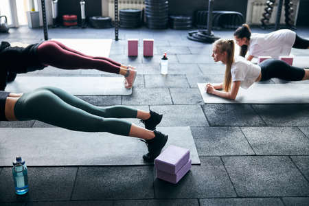 Cropped photo of strong ladies practising planking and core endurance at the gym together Archivio Fotografico