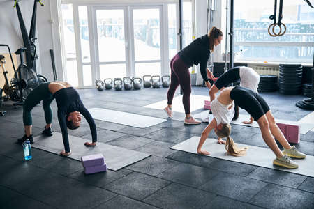 Helpful fitness instructor assisting ladies with correct positioning during bodyweight exercises