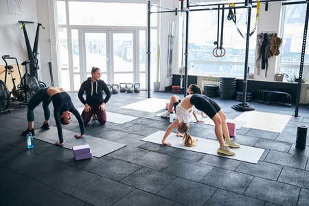 Proud female coach smiling while wathing her trainees perform bridge exercises on gym floor