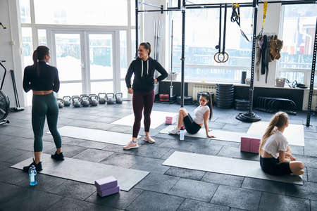Motivated young women feeling great while exercising at well-equipped gym