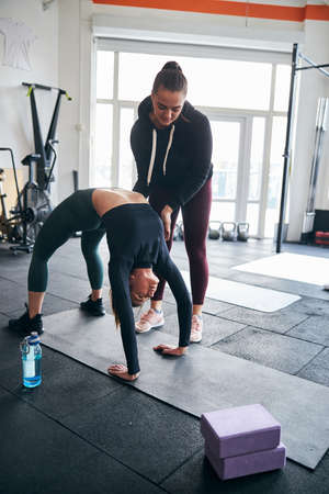 Qualified fitness instructor supporting a young woman while doing an upside down brifge exercise