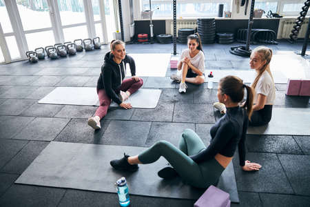 Slim young women sitting on their fitness mats at gym and having a conversation Archivio Fotografico