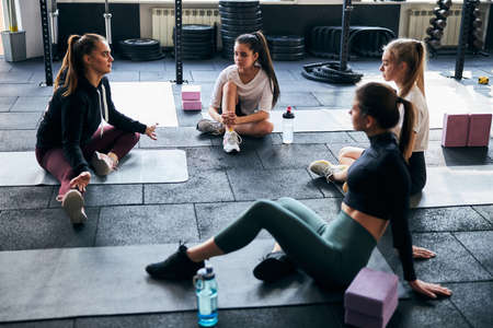 Young female fitness coach shrugging shoulders while discussing something with young women at the gym