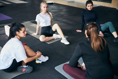 Serious young women sitting on gym floor and having a sports-related discussion