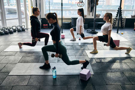 Side-view photo of a group of strong young doing lunges with extra dumbbell weight Archivio Fotografico