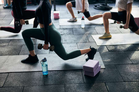 Cropped photo of energetic women doing lunges while holding dumbbells to the sides