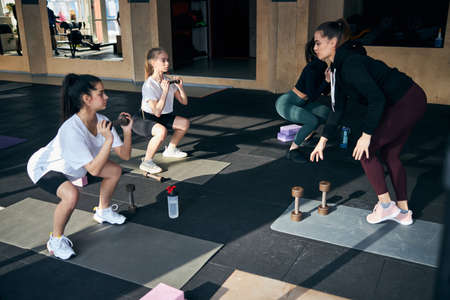 Serious young female athletes holding dumbbells and squatting while listening to their coach Archivio Fotografico