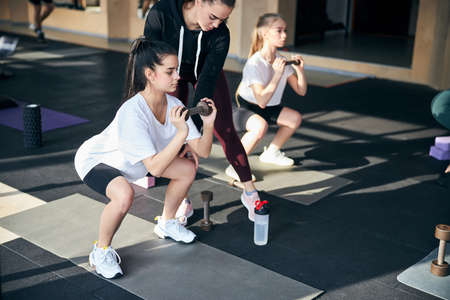 Professional fitness instructor correcting the squatting position of a young brunette athletic lady