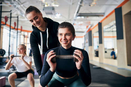 Joyous brunette lady smiling while squatting with a dumbbell and being guided by her friend